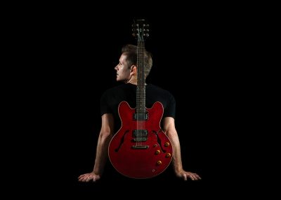 A portrait of Tom Barlow and his guitar resting upright on his back.